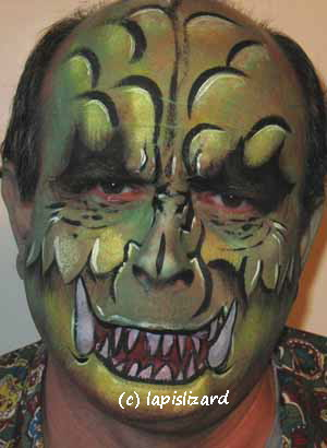 face painted as a green monster with big teeth